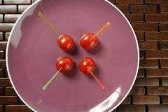 Tomatoes snack in a purple dish and colored sticks Stock Image