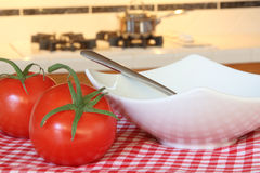 Tomatoes and a soup bowl with a cooking pan in the background. Making tomato soup on the stove in a blurred background with ripe red tomatoes in the foreground Stock Photography
