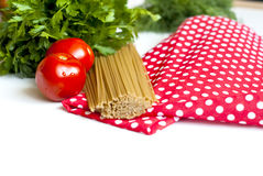 Tomatoes and spaghetti. Spaghetti, garlic, cherry tomatoes & lettuce on a wooden chopping board Stock Photos