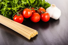 Tomatoes spaghetti garlic and parsley on wood. A bunch of spaghetti, some cherry tomatoes, parsley and garlic on a dark surface Stock Photo