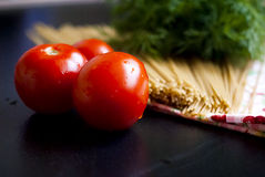 Tomatoes and spaghetti Stock Images