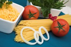 Tomatoes, spaghetti, onions and herbs Stock Photos
