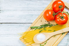 Tomatoes, spices and uncooked pasta Stock Photo