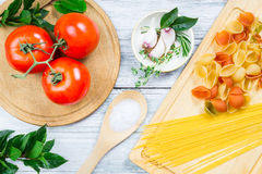 Tomatoes, spicies and uncooked assorted pasta Royalty Free Stock Images