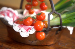 Tomatoes and spring onions in a copper pan Royalty Free Stock Photography