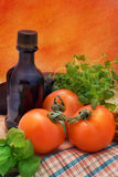 Tomatoes, still life. Fresh tomatoes on the table with olive, basil and oregano. Still life Royalty Free Stock Photo