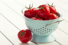 Tomatoes on a strainer. Some red tomatoes on a turquoise strainer on a white wooden table Royalty Free Stock Images