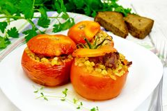 Tomatoes stuffed with bulgur and meat in plate on table Royalty Free Stock Image