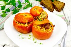 Tomatoes stuffed with bulgur in plate on table Royalty Free Stock Photo