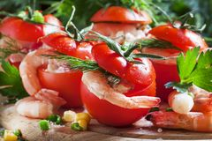 Tomatoes stuffed with shrimp meat and corn on a wooden plate, se stock photography