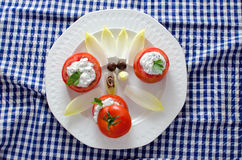 Tomatoes Stuffed. Stuffed tomatoes on a white plate on a blue checkered tablecloth Stock Photo