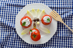 Tomatoes Stuffed and Wooden Fork. Stuffed tomatoes on a white plate on a blue checkered tablecloth Royalty Free Stock Image
