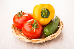 Tomatoes, sweet pepper and cucumber in wicker basket on table Royalty Free Stock Photo