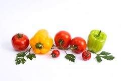 Tomatoes and sweet peppers on a white background. Red and yellow peppers on a white background. Tomatoes with colorful peppers in royalty free stock images