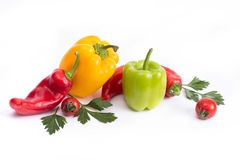 Tomatoes and sweet peppers on a white background. Red and yellow peppers on a white background. Tomatoes with colorful peppers in royalty free stock image