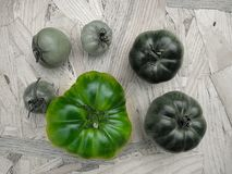 Tomatoes on a table in contrast colors green, black and white. Tomatoes on a table in contrast colors green, red, black and white. Harvest of autumn background Royalty Free Stock Photo