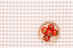 Tomatoes on the table and put it in a basket Royalty Free Stock Photography