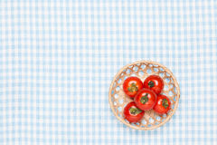 Tomatoes on the table and put it in a basket Royalty Free Stock Photos