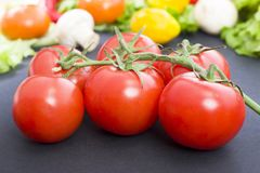 Tomatoes on the table. Red tomatoes lie on the old table. Dietary food. Tomatoes on the table on the background of vegetables. Royalty Free Stock Image