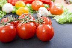Tomatoes on the table. Red tomatoes lie on the old table. Dietary food. Tomatoes on the table on  the background of vegetables. Tomatoes on the table. Red Stock Photography