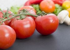Tomatoes on the table. Red tomatoes lie on the old table. Dietary food. Tomatoes on the table on the background of vegetables Royalty Free Stock Photos