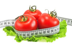 Tomatoes with tape measure and lettuce Stock Photo