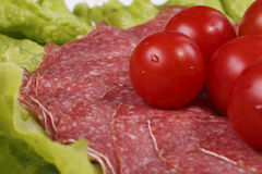 Tomatoes are on thin slices of salami. And lettuce Royalty Free Stock Photos