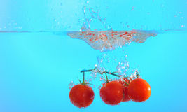 Tomatoes thrown in water Stock Photo