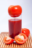 Tomatoes tomato juice on the cutting board. Tomatoes and a glass of tomato juice on the cutting board Royalty Free Stock Photo