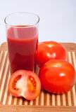 Tomatoes and tomato juice. Tomatoes and a glass of tomato juice on the cutting board Royalty Free Stock Images