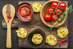 Tomatoes, tomato sauce, pasta, rosemary, red pepper for cooking dishes on a dark background. Top View. Royalty Free Stock Photo