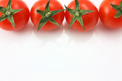 Tomatoes on top edge. Baby tomatoes on a white background stock image