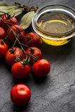 Tomatoes twig with bay leaf and olive oil on the dark stone table Stock Photo