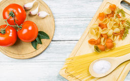 Tomatoes and uncooked assorted pasta Stock Photo