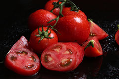 Tomatoes under water drops, red background royalty free stock images