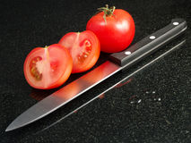 Tomatoes with vegetable knife Royalty Free Stock Images