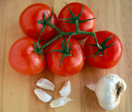 Tomatoes on vine with Garlic Stock Image