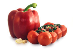 Tomatoes on the vine and red pepper. Delicious and nutritious vegetables: ripe tomatoes on the vine with a red pepper and cloves of garlic Stock Photo