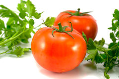 Tomatoes. On a white background with green Royalty Free Stock Photo