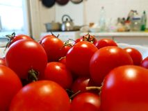 Tomatoes in a white bowl on the background of the kitchen. Whole tomatoes red. Red vegetablesSummer food.Tasty stock photo