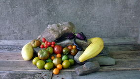 Tomatoes 34. Tomatoes, white cucumbers and stones on wooden table Royalty Free Stock Photo
