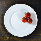 Tomatoes in white plate. On a wooden background royalty free stock photography
