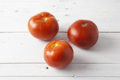 Tomatoes on a white table Stock Photo