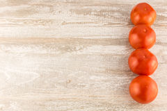 Tomatoes on a white wooden background close up copy space. Royalty Free Stock Images