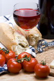 Tomatoes and wine. A tasty rustic platter of french bread, vine tomatoes and red wine royalty free stock photo