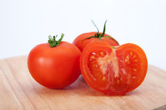 Tomatoes on the wood. Background stock image
