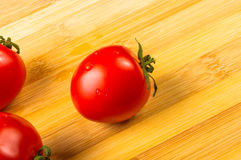 Tomatoes on wooden background Royalty Free Stock Images