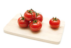 Tomatoes on a wooden board. Fresh tomatoes on a wooden board on white background royalty free stock photography