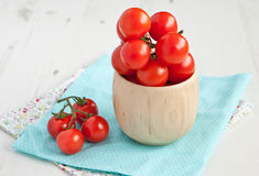 Tomatoes in wooden bowl on the whte table Stock Image