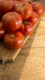 Tomatoes on wooden chopping board. And table Stock Photo